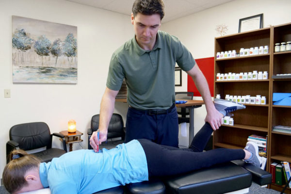 Chiropractor Dr Riley using Applied Kinesiology (manual muscle testing) at Needham MA office near Boston
